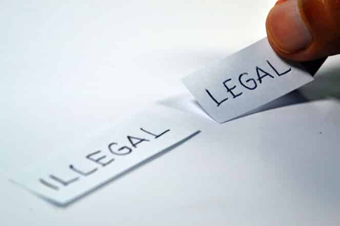 a person holding words legal and illegal written on small pieces of papers