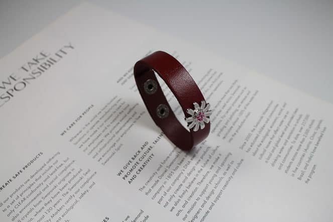 a brown colored bracelet kept on a contract paper